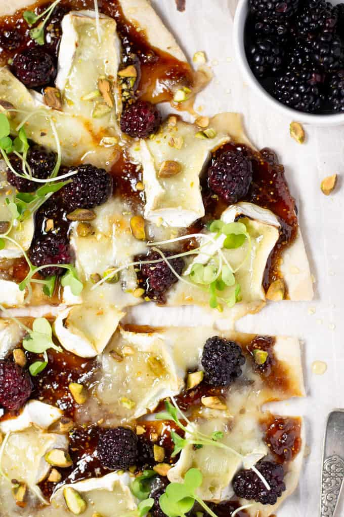 Overhead shot of a brie and blackberry flatbread on a cutting board garnished with microgreens