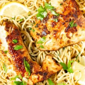 Close up shot of lemon butter cod served with spaghetti and garnished with fresh parsley