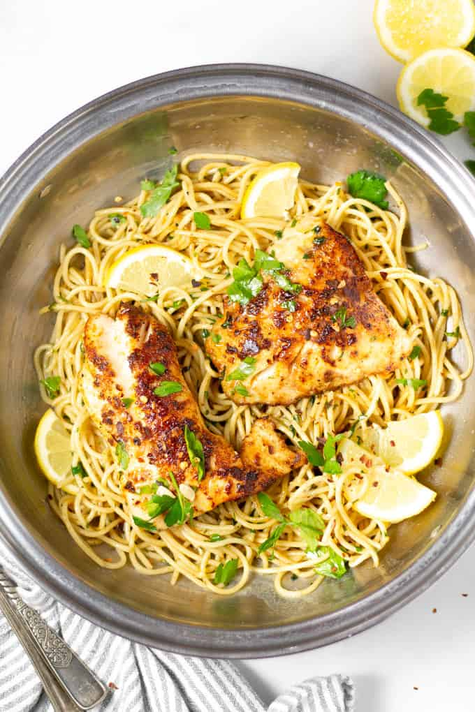 Overhead shot of lemon butter fish with spaghetti in a silver pot garnished with fresh chopped parsley