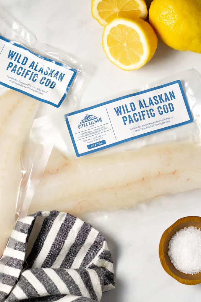 A white marble counter top with two packages of fresh fish and sliced lemons