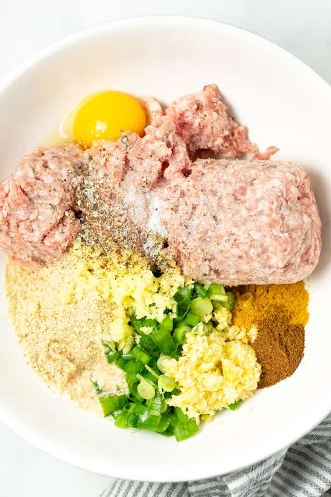 Overhead shot of a white bowl filled with ingredients to make pork meatballs