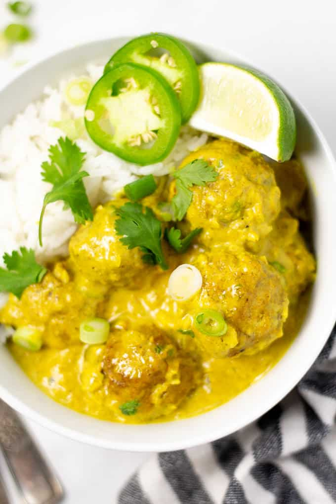 Close up shot of curried pork meatballs garnished with fresh cilantro on a bed of white rice