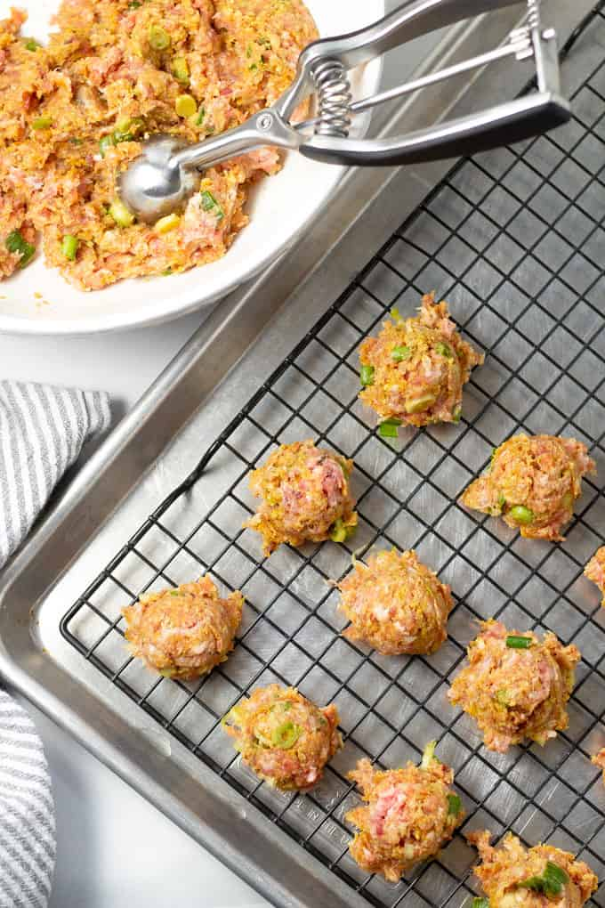 Baking sheet with a cooling rack on top and a cookie scoop scooping meatballs