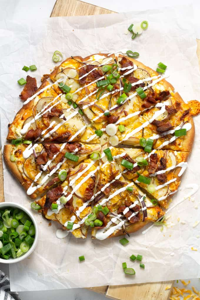 Overhead shot of a baked potato pizza garnished with sour cream and green onion