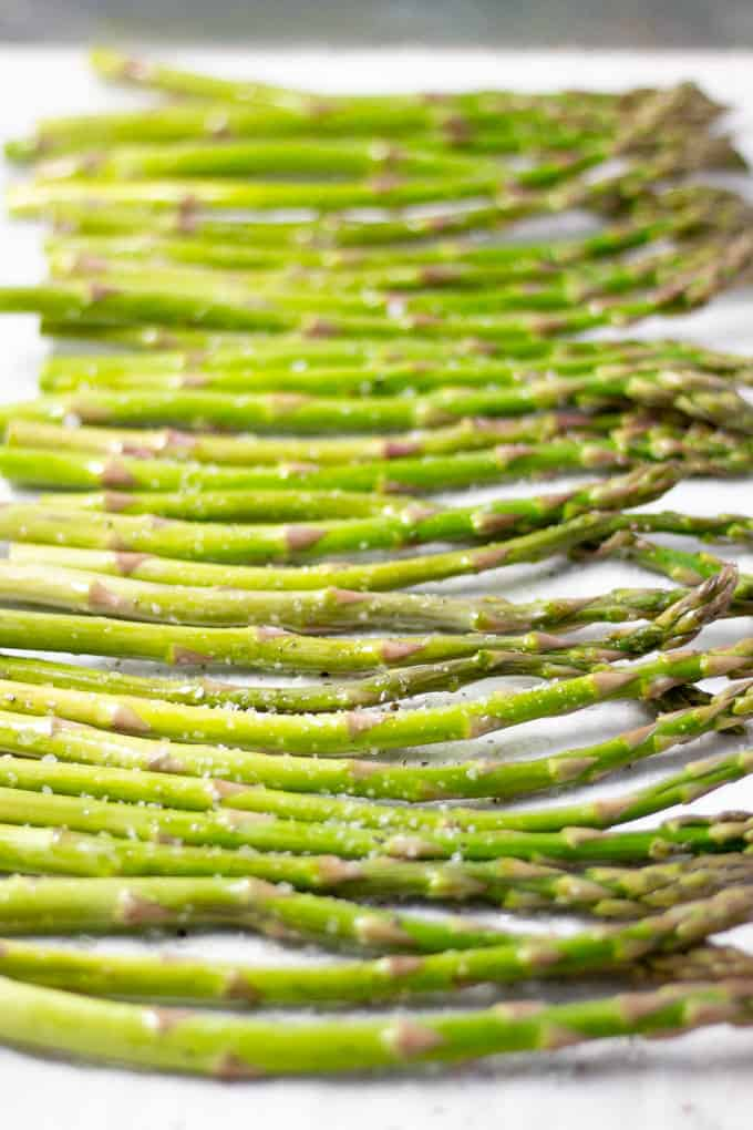 Parchment lined baking sheet with fresh asparagus seasoned with salt and pepper