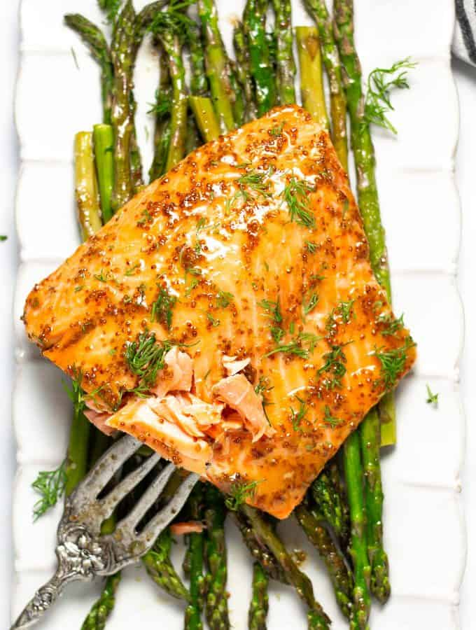 A large white platter filled with asparagus and sheet pan honey mustard salmon
