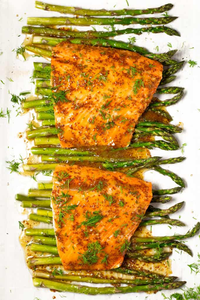 White parchment paper lined baking sheet with roasted asparagus and sheet pan salmon