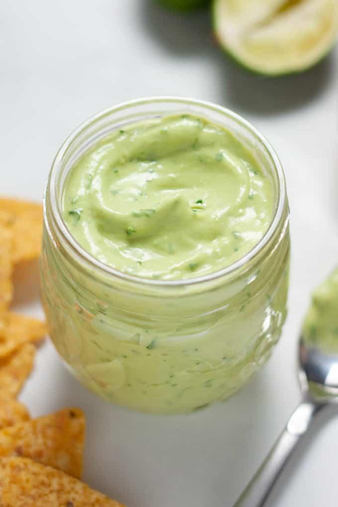 Close up shot of a small mason jar filled with cilantro lime avocado sauce