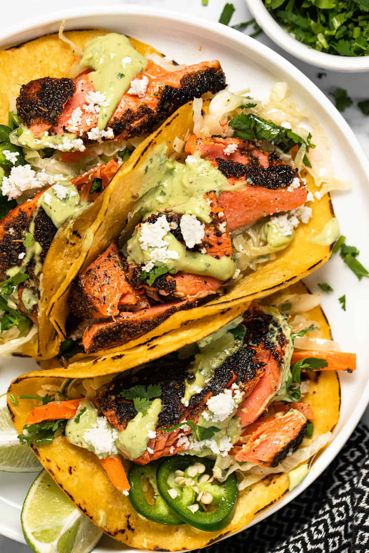 White plate with blackened salmon tacos garnished with cilantro