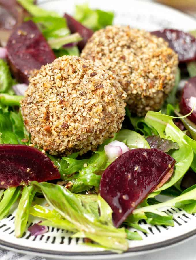 Close up shot of baked goat cheese on a green salad with sliced beets