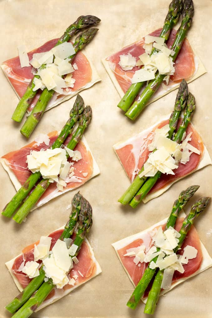 Parchment paper with 6 squares of puff pastry topped with prosciutto asparagus and Parmesan