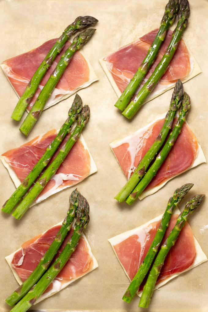 Parchment paper with 6 squares of puff pastry topped with prosciutto and asparagus