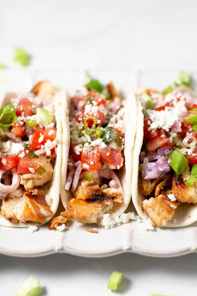 Close up shot of a three chicken tacos in flour tortillas garnished with fresh pico de gallo