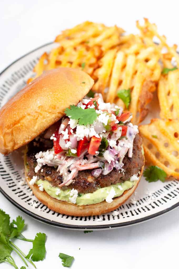 Close up shot of a Mexican burger loaded with chipotle slaw and pico de gallo