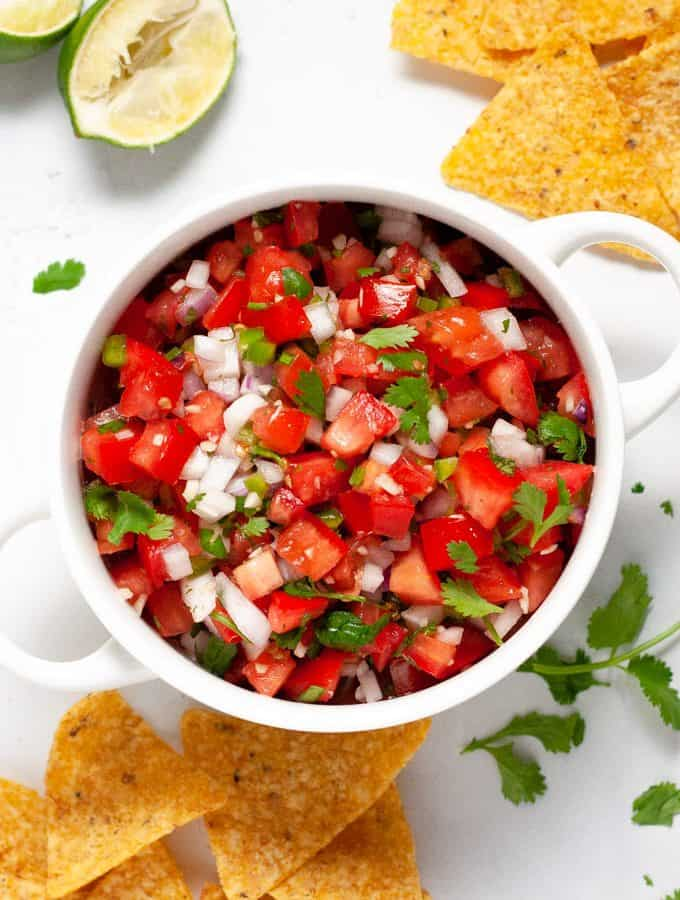 Overhead shot of a white bowl filled with homemade pico de gallo surrounded by chips