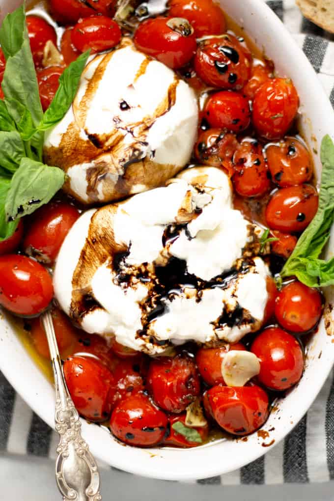 Overhead shot of a white platter filled with roasted tomatoes and burrata garnished with fresh basil
