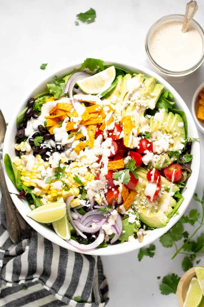 Overhead shot of Southwest salad loaded with fresh veggies in a white bowl on a white counter top