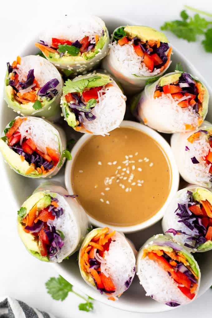 Overhead shot of a white platter filled with spring rolls and peanut sauce