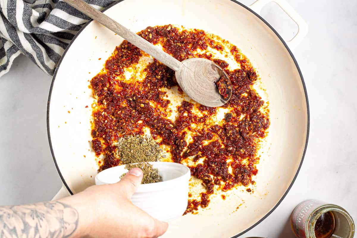 Large white pan with minced sun dried tomato and dried herbs