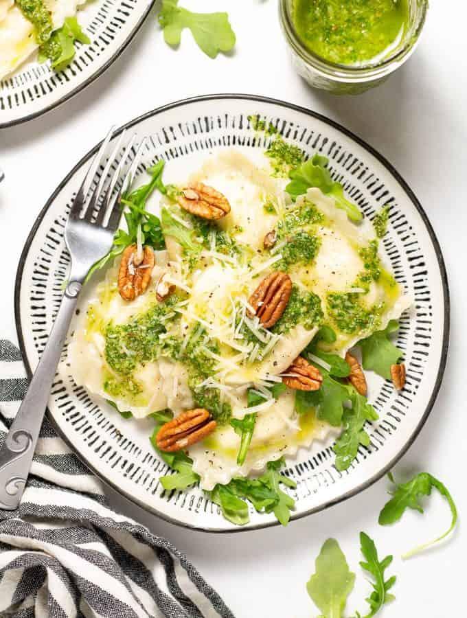 Overhead shot of a white plate filled with wonton ravioli and arugula pesto