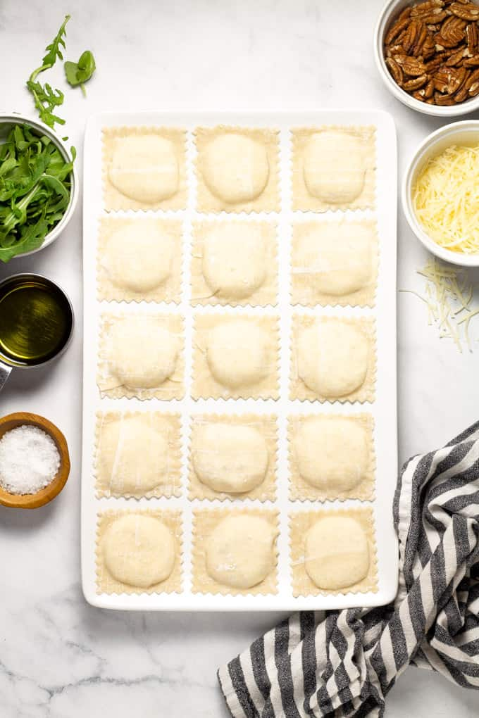 Overhead shot of a large white platter filled with homemade wonton ravioli