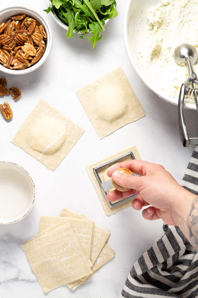 Overhead shot of a white marble counter top with wonton ravioli being stamped with a ravioli stamp