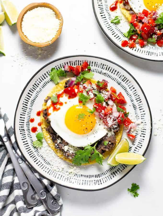 Mexican breakfast tostada on a white and black plate garnished with fresh cilantro and pico de gallo