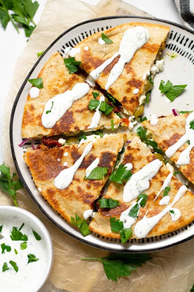Overhead shot of a Greek quesadilla on a white plate drizzled with homemade tzatziki sauce