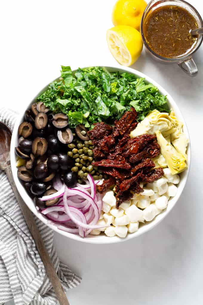 Overhead shot of a white bowl filled with ingredients to make Mediterranean pasta salad