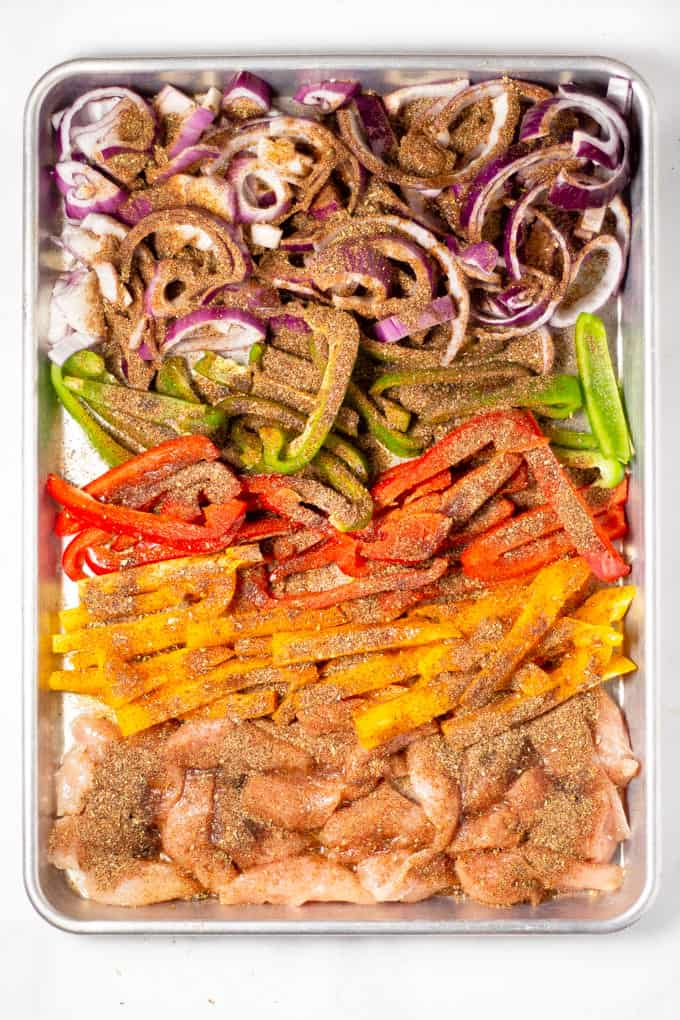 Sheet pan filled with chicken peppers and onions sprinkled with seasoning for sheet pan fajitas