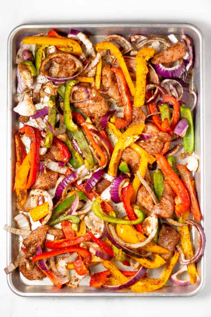 Sheet pan filled with chicken peppers and onions tossed with oil and seasonings for sheet pan fajitas