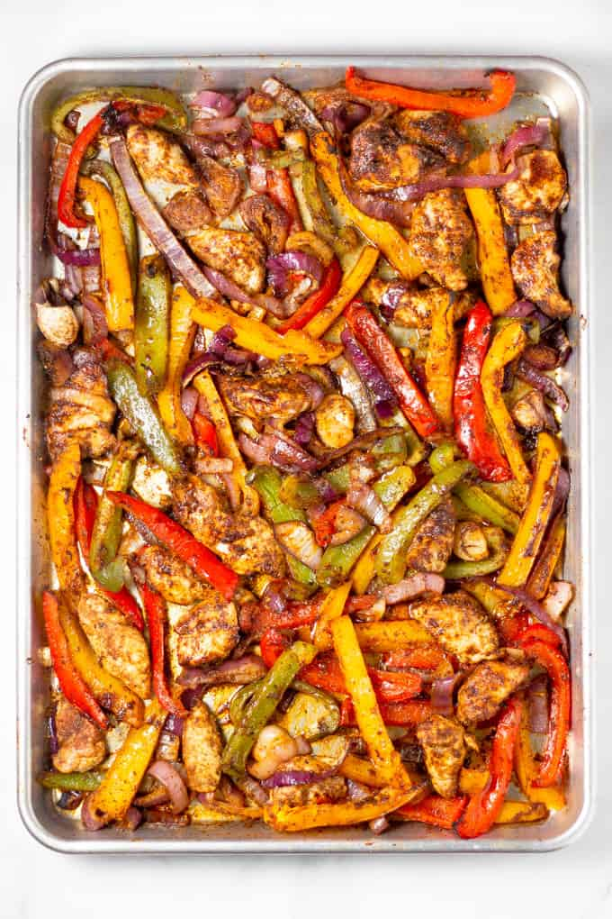 Sheet pan filled with baked chicken peppers and onions for sheet pan fajitas