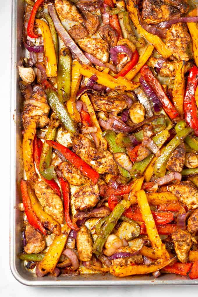 Close up shot a  sheet pan filled with chicken peppers and onions for sheet pan fajitas