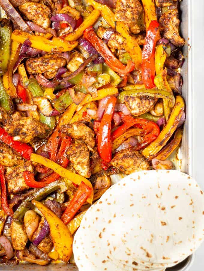 Overhead shot of a metal sheet pan loaded with peppers onions and chickens with flour tortillas