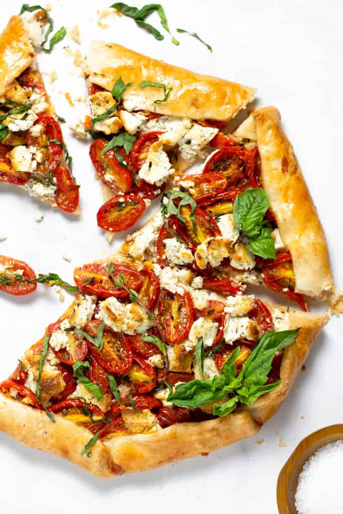 Overhead shot of a freshly baked tomato tart on a white marble counter top garnished with fresh basil