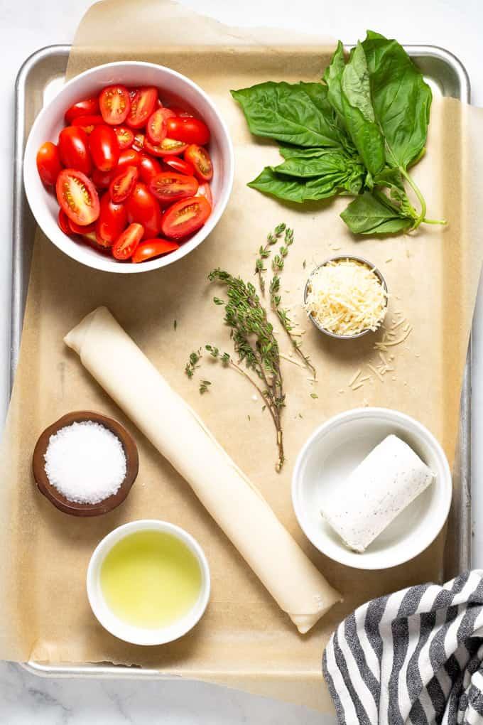 Baking sheet filled with ingredients to make tomato tart