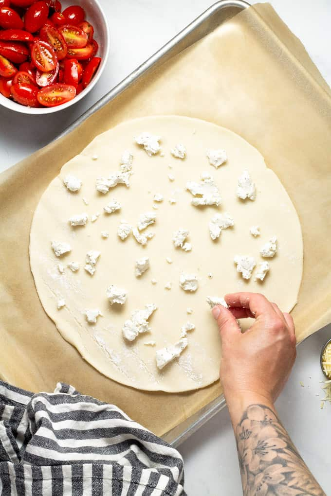 Pie crust on a baking sheet being topped with crumbled goat cheese