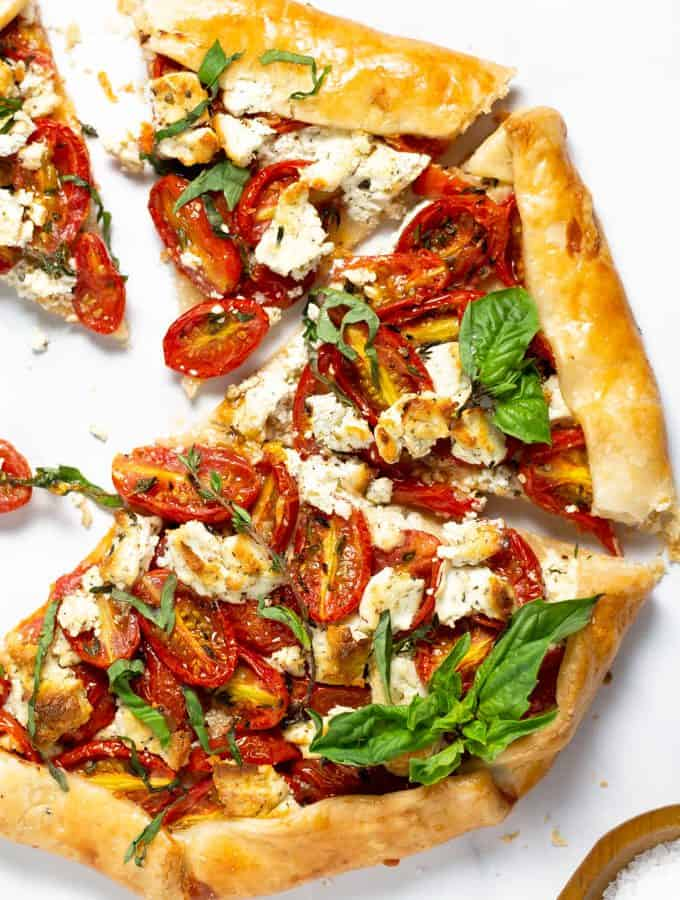 Overhead shot of a tomato galette on a white marble counter top garnished with fresh basil