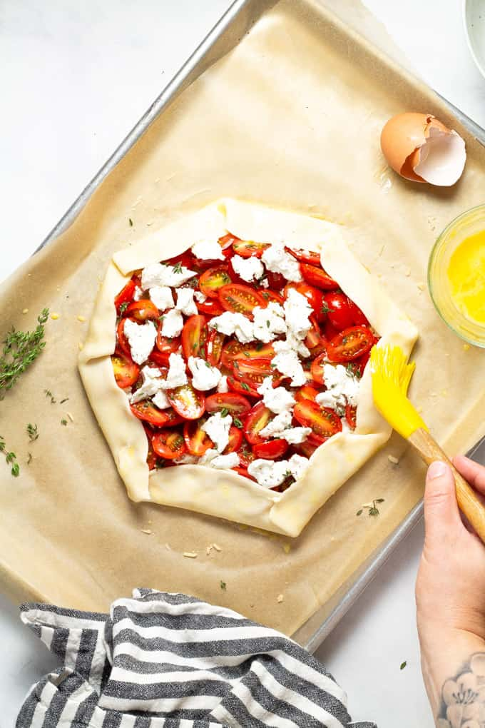 Tomato tart on a parchment lined baking sheet with the crust being brushed with egg wash