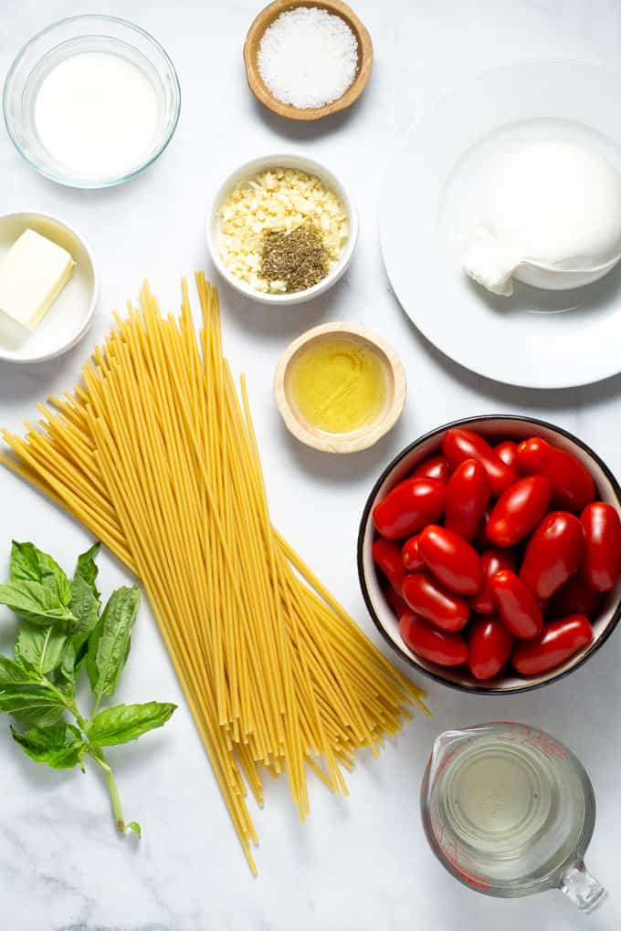A white marble counter top filled with ingredients to make tomato and garlic pasta