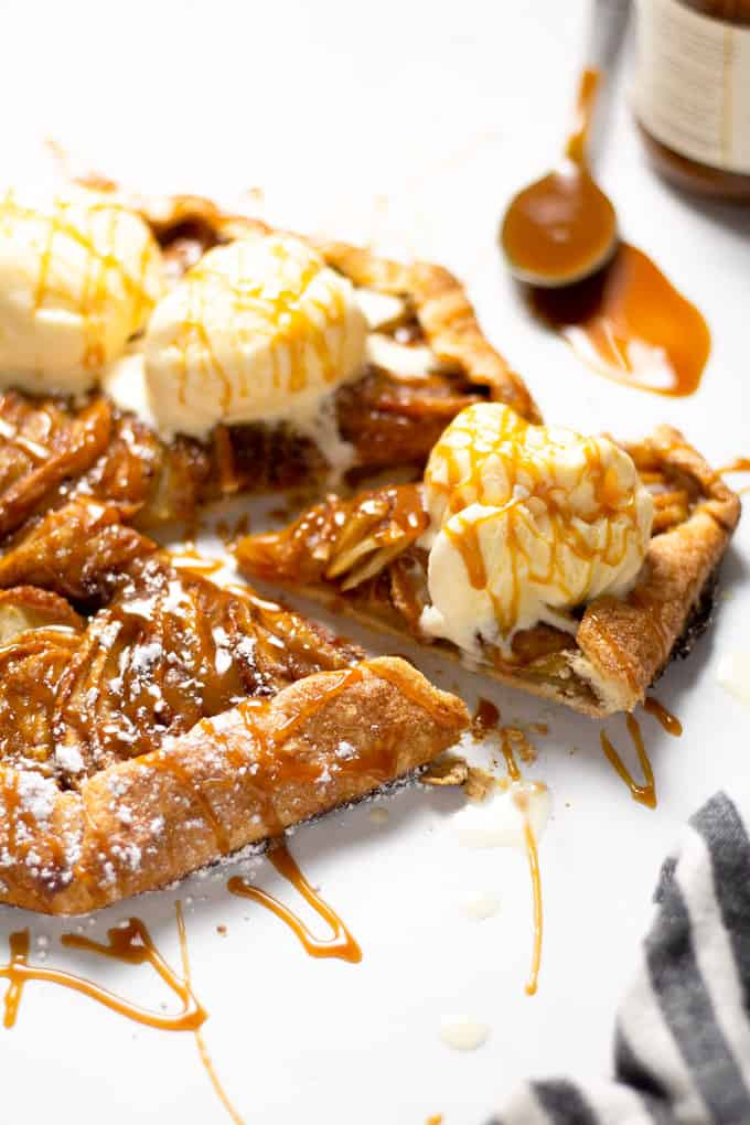 Close up shot of a slice of an apple tart topped with caramel and ice cream