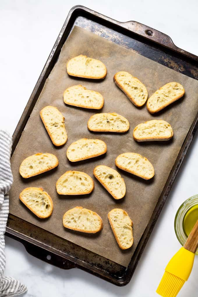 Slices of French baguette on a parchment lined baking sheet