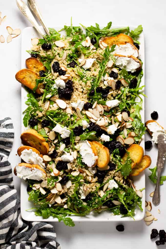 White serving platter filled with arugula salad with goat cheese dried cherries and almonds