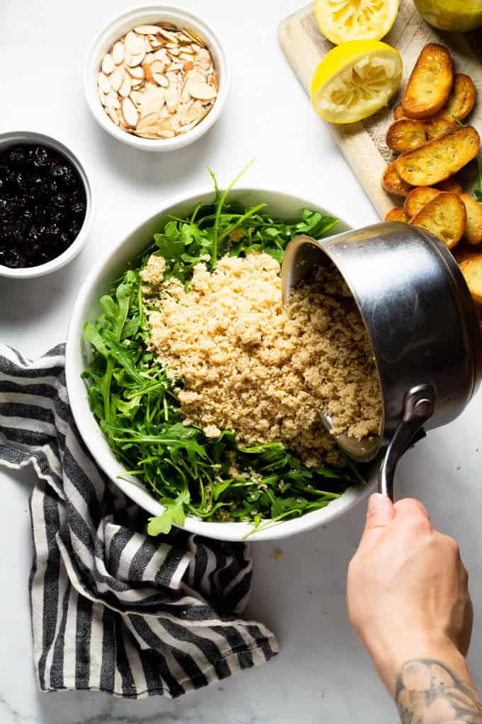 A white bowl filled with arugula and a saucepan of cooked couscous being poured over it