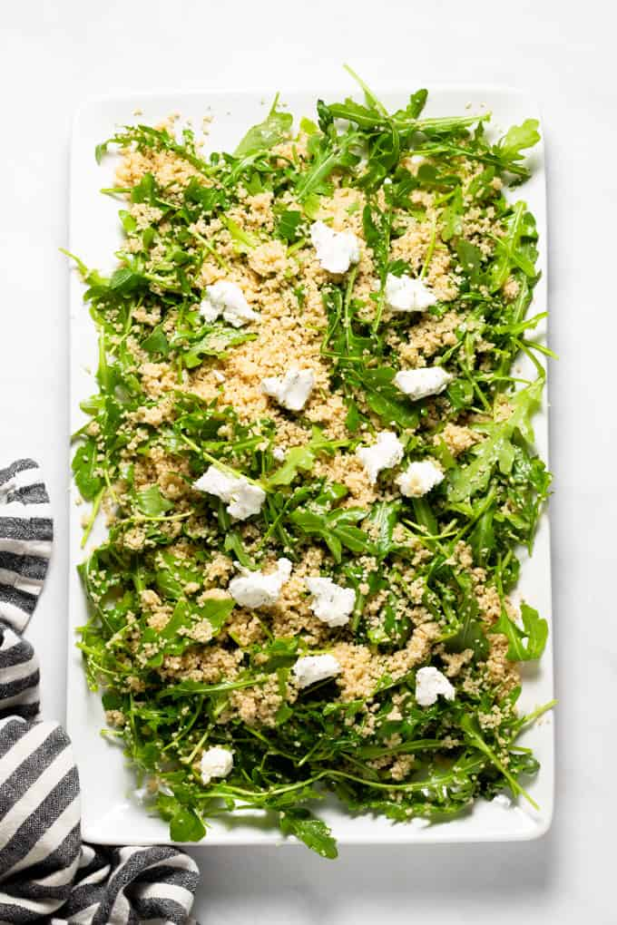 White serving platter filled with arugula salad with couscous and goat cheese
