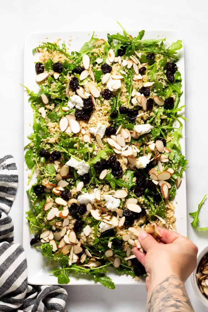 White serving platter filled with arugula salad with couscous goat cheese cherries and almonds