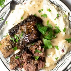 Overhead shot of a white plate filled with homemade mashed potatoes and beer braised beef short ribs