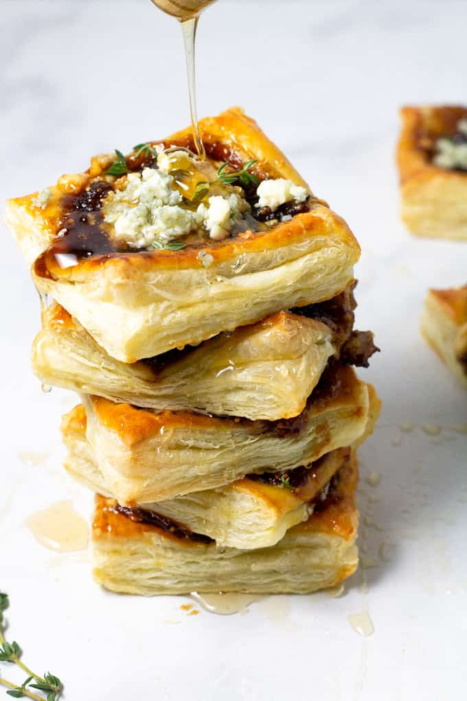 Puff pastry tarts stacked on a counter top with honey being drizzled over it