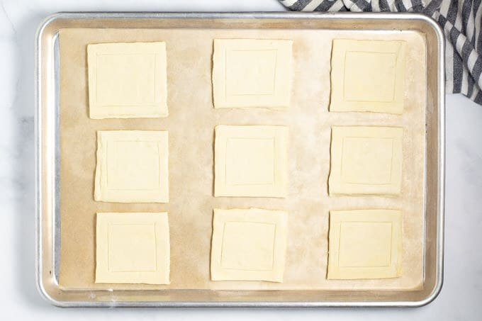 A parchment lined baking sheet with squares of puff pastry on it