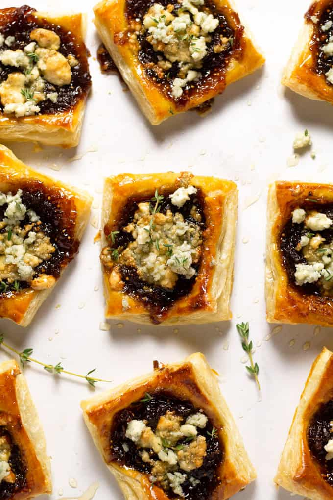 Overhead shot of a white counter top with caramelized onion tarts on it